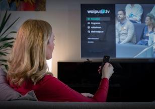 Eine Frau schaut auf ihrem Fernseher eine Sendung